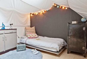 Teenager's bedroom with white awning and fairy lights over bed