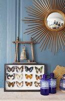 Collection of mounted butterflies and prayer bell below sunburst mirror