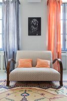 Peach cushions on comfortable retro sofa in front of portrait of woman and curtains in two different shades