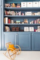 Dove-grey fitted cupboards with books and ornaments on open bookshelves
