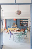Round table, pastel chairs and dove-grey fitted cupboards in living area