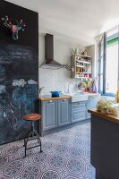 Ornamental floor tiles and drawings on chalkboard wall in country-house kitchen