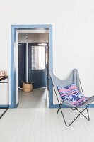Butterfly Chair on white wooden floor and view into hallway