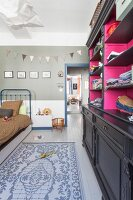 Bed, metal toys and black vintage cabinet with hot pink interior in child's bedroom