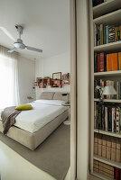 Blick entlang eines Bücherregals ins Schlafzimmer in Beige