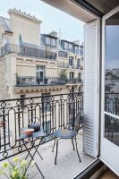 Metal furniture on balcony with view of house opposite