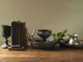 Still-life arrangement of books, goblets, bowls, jug and roses
