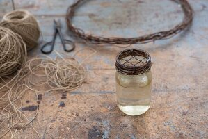 Glas mit Flüssigkeit und Metalldeckel vor Paketschnur und Drahtkranz