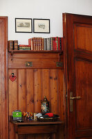 Console table against wainscoting below bookshelf