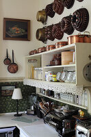 Old cake tins and pans on wall above shelves in kitchen