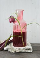 Snake's head fritillary leant against vintage carafe of red drink