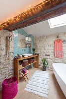 Exposed masonry and wooden washstand against blue tiles in bathroom