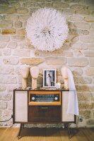 Juju hat on stone wall above retro radio