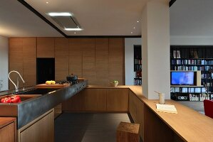 Offene Designerküche aus Holz mit Metallspüle und integriertem Pfeiler; Blick in Wohnbereich mit Regalwand