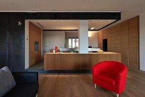 Moderne Küche mit schlichten Holzfronten in offenem Wohnbereich mit rotem Armlehnsessel und schwarzer Metall-Wandverkleidung