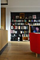 Black metal bookcase with integrated TV in open-plan living space with oak parquet floor