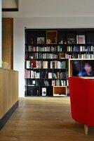 Schwarzes Metall-Bücherregal mit integiertem Fernseher in offenem Wohnbereich mit Eichenparkett