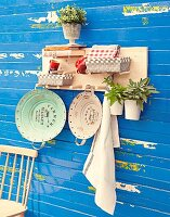 Hand-crafted, wall-mounted shelf with wooden pegs for holding baskets, books and various objects
