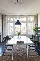 Schlichter Esstisch im Altbau mit Stuckdecke und Buntglasfenstern