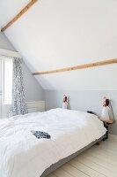 Schlichtes Schlafzimmer unter dem Dach in Weiß und hellem Grau