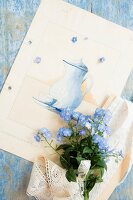 Posy of forget-me-nots on card with picture of coffee pot