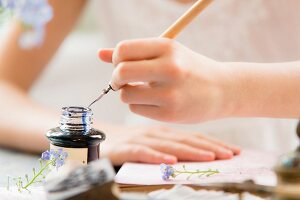Hand dipping quill pen into ink pot