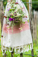 Bouquet of wildflowers and cotton towel hung on garden fence