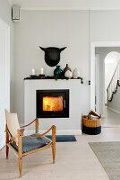 Old designer chair in front of lit fire in square stove