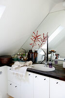 Vintage ornaments in bathroom under sloping ceiling with mirrored wall