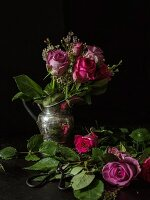 Silver jug of roses against black background