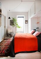 Red blanket on bed surrounded by fitted cabinets