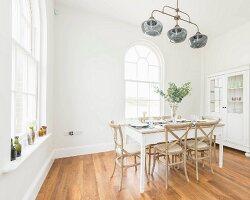 Weisses Esszimmer mit Rundbogenfenstern und gedecktem Esstisch in Altbauwohnung