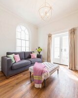 A reduced living area with an upholstered table and couch in front of round arched windows