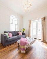 Reduzierter Wohnbereich mit Polstertisch und Couch vor Rundbogenfenster