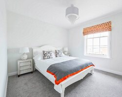 A white double bed with a headboard in front of lattice windows with retro orange blinds