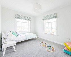 Weisses Bett und buntes Holzspielzeug auf grauem Teppichboden