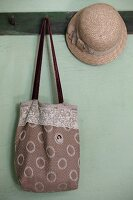 Bag with vintage-style embroidered medallion next to straw hat