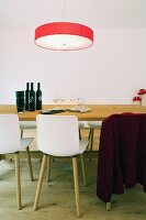 Red lampshade above simple wooden table and modern chairs