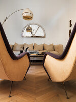 Two retro armchairs in front of coffee table and beige sofa