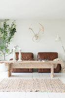 Rustic coffee table in front of two brown leather armchairs