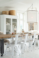 Long dinning table and white chairs in front of open-fronted dresser