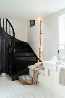 Black staircase in white kitchen with bench integrated into kitchen counter