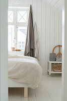 View into bedroom in pale natural shades with white board wall