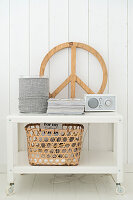 Basket, CND symbol and radio on trolley against white board wall