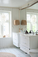Bright, white bathroom with twin sinks against large mirror