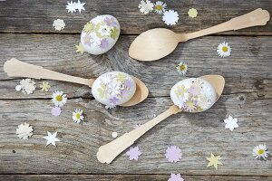 Mit ausgestanzten Blümchen verzierte Eier auf Holzlöffeln