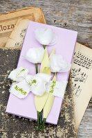 Gebastelte Papierblumen auf einer Schachtel aus Papier