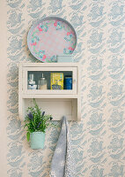 Pot of lavender hung from vintage kitchen cabinet on patterned wallpaper