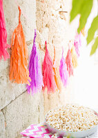 Garland of hand-made tassels on wall and bowl of popcorn