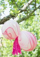 Marmorierte Luftballons am Baum hängend